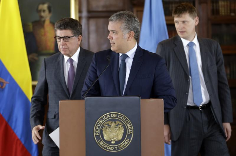 Peruvian Ambassador Gustavo Meza-Cuadra, the president of UN Security Council, from left, Colombia's President Ivan Duque, and British Ambassador Jonathan Guy, arrive to deliver a joint statement to reporters in Bogota, Colombia, Friday, July 12, 2019. The U.N. council is in Colombia for a firsthand look at implementation of the 2016 peace agreement between the government and the country's main rebel group. (AP Photo/Fernando Vergara)