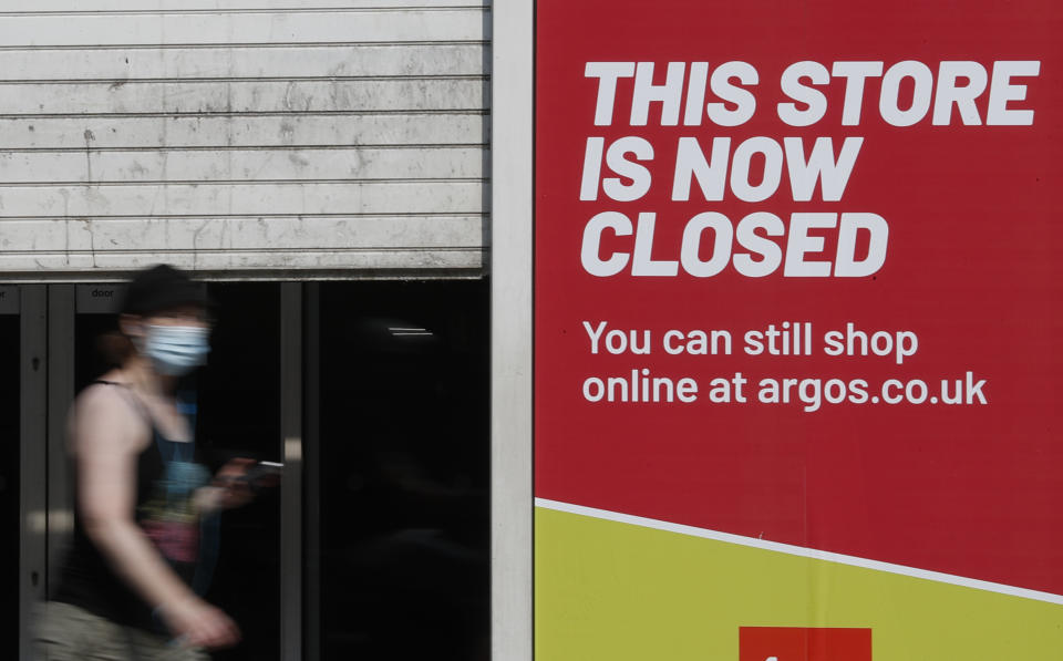 A woman looks at her phone as she walks past a closed branch of a shop in Kensington, London, Wednesday, Aug. 12, 2020. The British economy is on course to record the deepest coronavirus-related slump among the world's seven leading industrial economies after official figures showed it shrinking by a 20.4% in the second quarter of 2020 alone said The Office for National Statistics. (AP Photo/Alastair Grant)