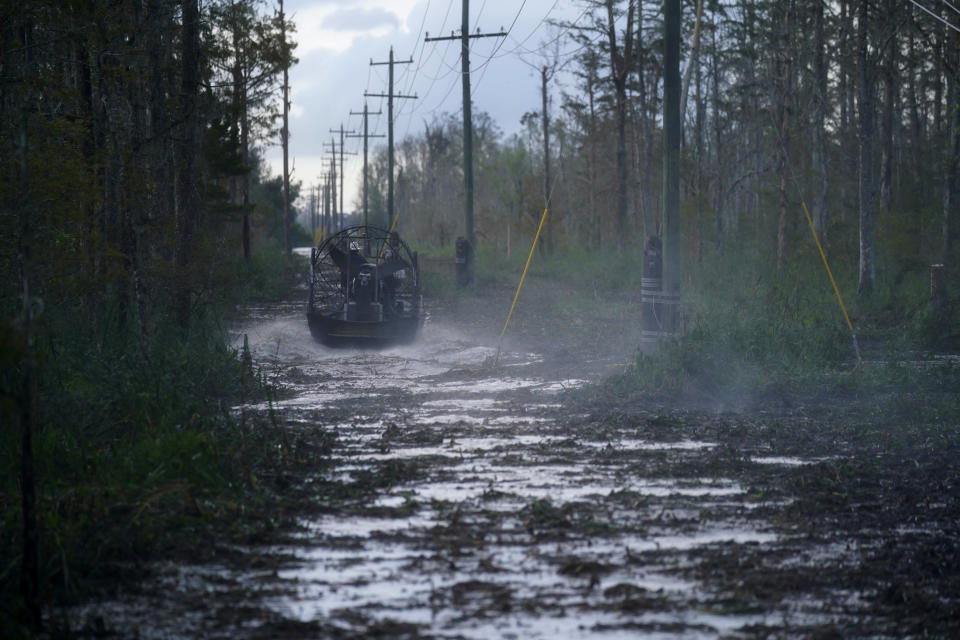 Electrical workers ride through marsh in an airboat to restore power lines in the aftermath of Hurricane Ida in Houma, La., Friday, Sept. 17, 2021. The Louisiana terrain presents special challenges. In some areas, lines thread through thick swamps that can be accessed only by air boat or marsh buggy, which looks like a cross between a tank and a pontoon boat. Workers don waders to climb into muddy, chest-high waters home to alligators and water moccasins. (AP Photo/Gerald Herbert)