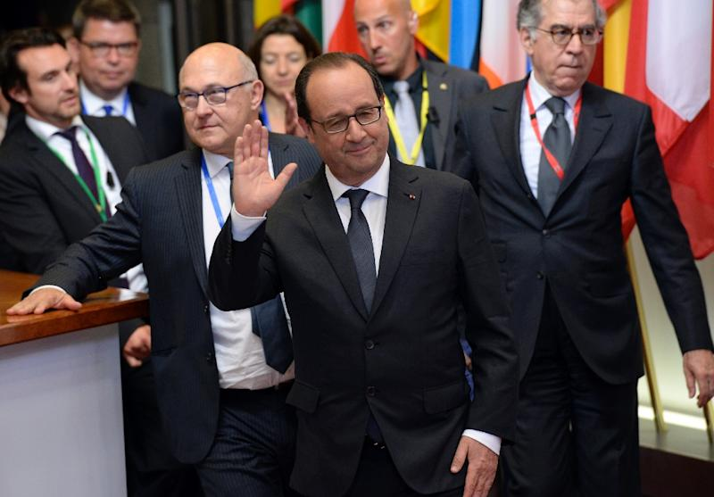 French President Francois Hollande (C) and Finance Minister Michel Sapin (L) leave after a special meeting about the Greek crisis, at the EU Council building in Brussels, on June 23, 2015 (AFP Photo/Thierry Charlier)