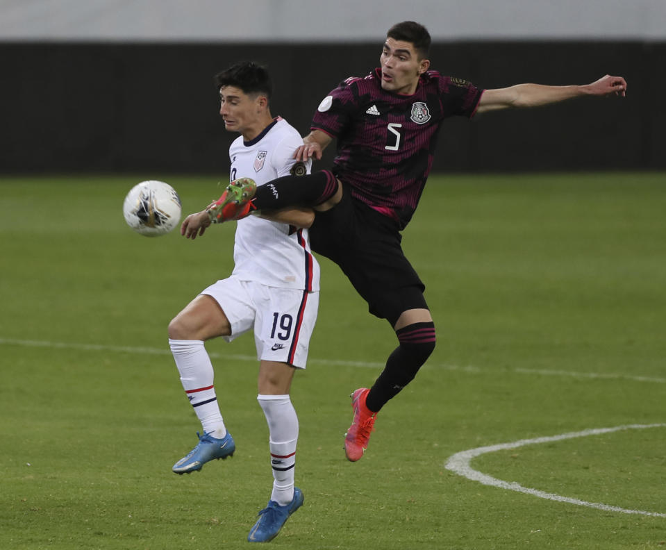 Mexico's Johan Vasquez (5) and United States' Sebastian Soto fight for the ball during a Concacaf Men's Olympic Qualifying championship soccer match in Guadalajara, Mexico, Wednesday, March 24, 2021. (AP Photo/Fernando Llano)
