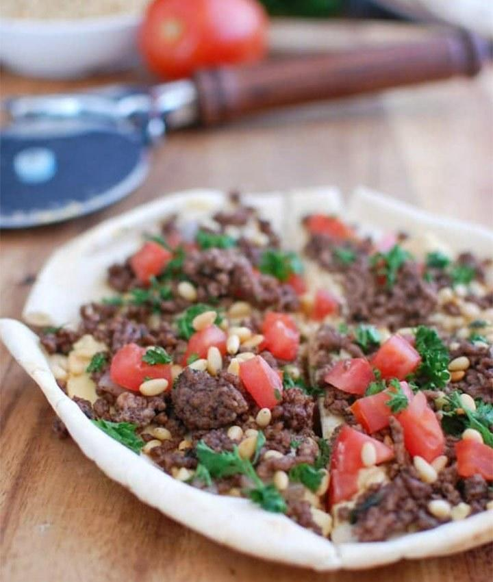 """For a Mediterranean take on pizza, this recipe calls for pita bread as your crust base. Top with seasoned ground beef, hummus, toasted pine nuts and tomatoes for a tasty dish that can work well as a meal or appetizer. It also incorporates ghee (clarified butter with lowered dairy fats and preserved nutrients like <a rel=""""nofollow noopener"""" href=""""https://www.eatthis.com/healthy-fats/?utm_source=yahoo-news&utm_medium=feed&utm_campaign=yahoo-feed"""" target=""""_blank"""" data-ylk=""""slk:healthy fats"""" class=""""link rapid-noclick-resp"""">healthy fats</a>), which can also be substituted with feta cheese for added protein and flavor. <strong>Get the recipe from <a rel=""""nofollow noopener"""" href=""""https://www.acedarspoon.com/spiced-beef-and-hummus-pita-pizza/"""" target=""""_blank"""" data-ylk=""""slk:A Cedar Spoon"""" class=""""link rapid-noclick-resp"""">A Cedar Spoon</a>.</strong>"""
