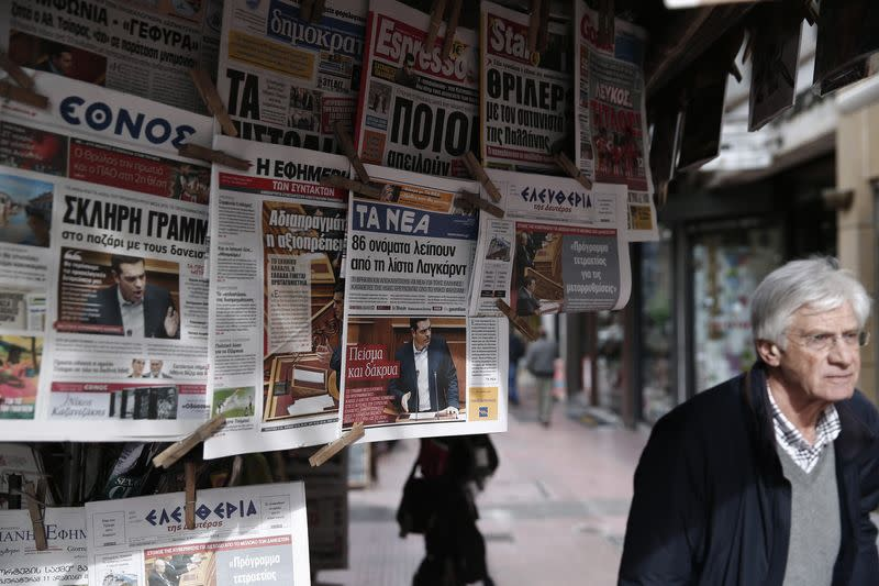 Greek Prime Minister Alexis Tsipras is pictured on newspapers at a kiosk in Athens