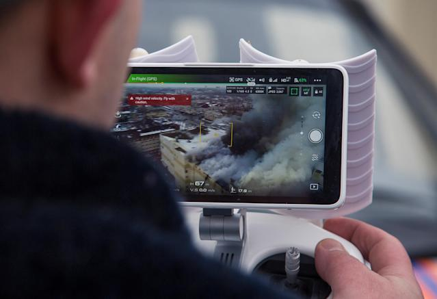 <p>A member of the Emergency Situations Ministry operates a drone at the scene of a fire in a shopping mall in the Siberian city of Kemerovo, Russia, on March 25, 2018. (Photo: Maksim Lisov/Reuters) </p>