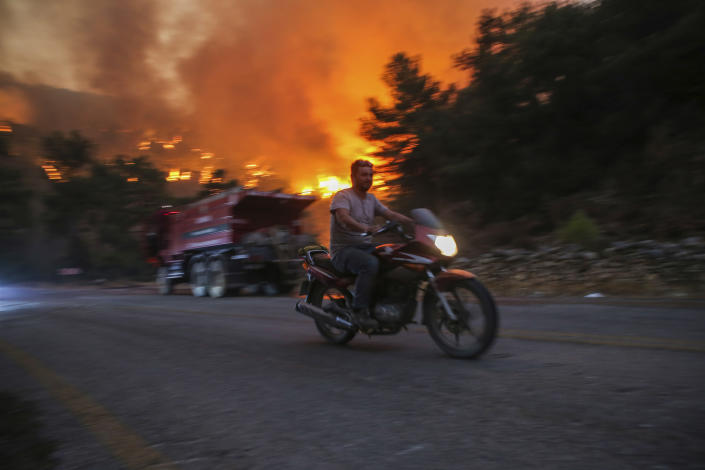 A man rides away from an advancing fire that rages Cokertme village, near Bodrum, Turkey, Monday, Aug. 2, 2021. For the sixth straight day, Turkish firefighters battled Monday to control the blazes that are tearing through forests near Turkey's beach destinations. Fed by strong winds and scorching temperatures, the fires that began Wednesday have left eight people dead. Residents and tourists have fled vacation resorts in flotillas of small boats or convoys of cars and trucks. (AP Photo/Emre Tazegul)