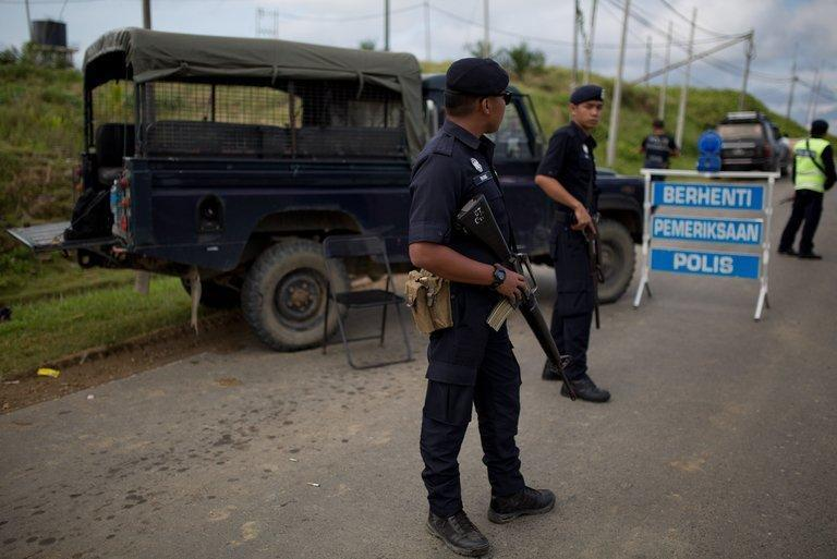 Malaysian armed policemen man a security check point in Cenderawasih on the Malaysian island of Borneo on March 3, 2013. Five Malaysian policemen and two gunmen have died in a fresh clash on Borneo island, as fears mounted that violence linked to a deadly standoff with Filipino intruders was spreading