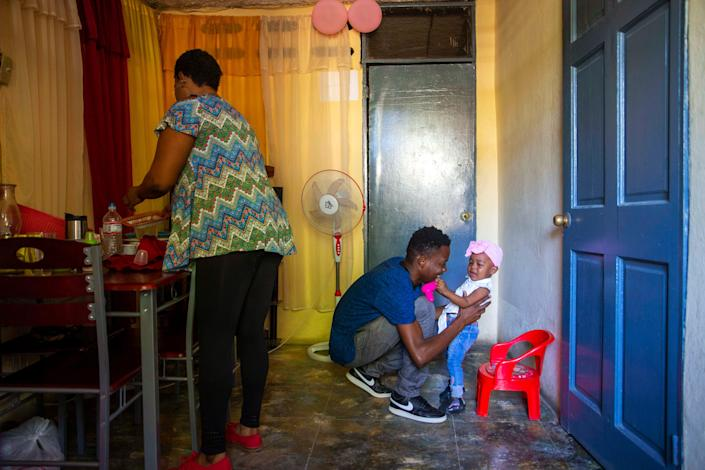 Verty plays with his 1-year-old daughter while his wife Saint Jean fixes the house in Port-au-Prince, Haiti, on Aug. 25, 2020. The Trump administration had sharply increased its use of hotels to detain immigrant children before expelling them from the United States during the coronavirus pandemic. Verty says government contractors at a hotel where he was detained gave his family, including his daughter, cups of ice to eat to pass temperature checks prior to their deportation flight, even though they had tested negative for COVID-19.