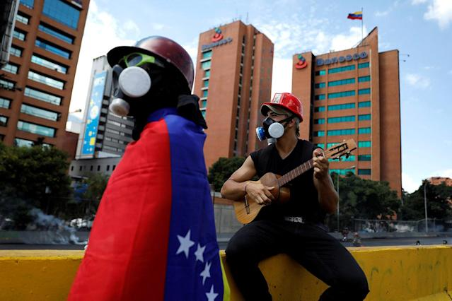 <p>A demonstrator plays a guitar during clashes at a march to the state Ombudsman's office in Caracas, Venezuela May 29, 2017. (Photo: Carlos Garcia Rawlins/Reuters) </p>