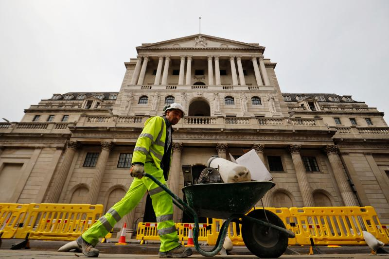 A worker pushes a wheelbarrow of debris outside the Bank of England in London on June 17, 2020. - The Bank of England, confronted by Britain's collapsing coronavirus-ravaged economy, will on June 18 reveal the outcome of its latest monetary policy meeting with analysts predicting more stimulus. The British central bank has been at the forefront of economic fire-fighting over this year's deadly COVID-19 emergency -- and could expand its quantitative easing (QE) stimulus in an attempt to kickstart growth. (Photo by Tolga Akmen / AFP) (Photo by TOLGA AKMEN/AFP via Getty Images)