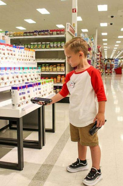 PHOTO: Cooper's 'duties' as a Target employee for the day included scanning merchandise on the shelves. (Hannah Rickman/Momgical Photography)