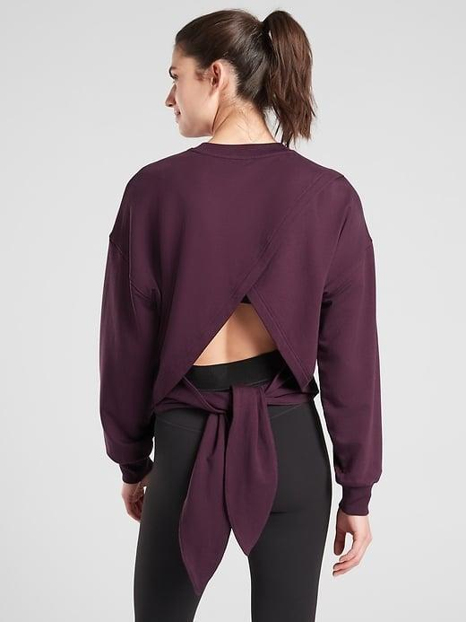 """<p>You'll definitely find yourself trying to catch a glimpse of this <span>Athleta Yoga Tie Back Sweatshirt</span> ($25-$56, originally $79) in the mirror as you work through different poses. Plus, the material is so soft, you just <a href=""""https://www.popsugar.com/fitness/Benefits-Savasana-44648879"""" class=""""link rapid-noclick-resp"""" rel=""""nofollow noopener"""" target=""""_blank"""" data-ylk=""""slk:may actually fall asleep during Savasana"""">may actually fall asleep during Savasana</a> this time.</p>"""