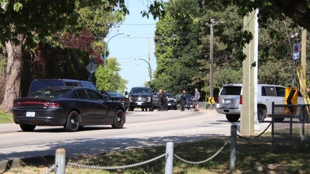 Vancouver police officers surround the area around Southwest Marine Drive and West 57th Avenue Saturday morning after reports of a man with a knife in the neighbourhood.  (Shane MacKichan - image credit)
