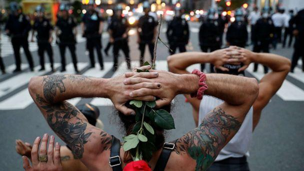 PHOTO: Protesters kneel in front of New York City Police Department officers before being arrested for violating curfew beside the iconic Plaza Hotel on 59th Street, June 3, 2020, in New York. (John Minchillo/AP)