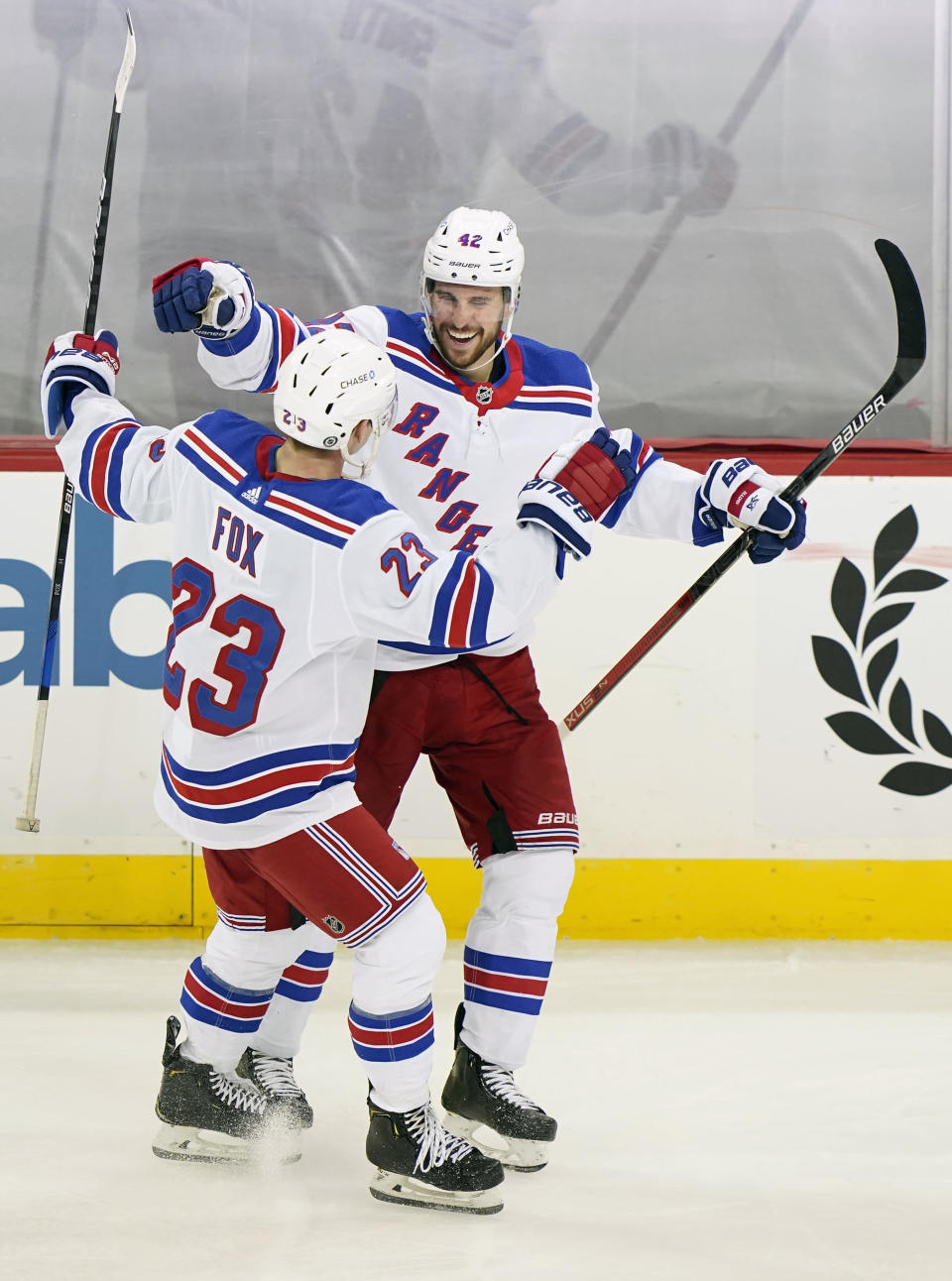 New York Rangers defenseman Brendan Smith (42) celebrates with Rangers defenseman Adam Fox (23) after scoring a goal during the third period of an NHL hockey game against the New Jersey Devils, Thursday, March 4, 2021, in Newark, N.J. (AP Photo/Kathy Willens)