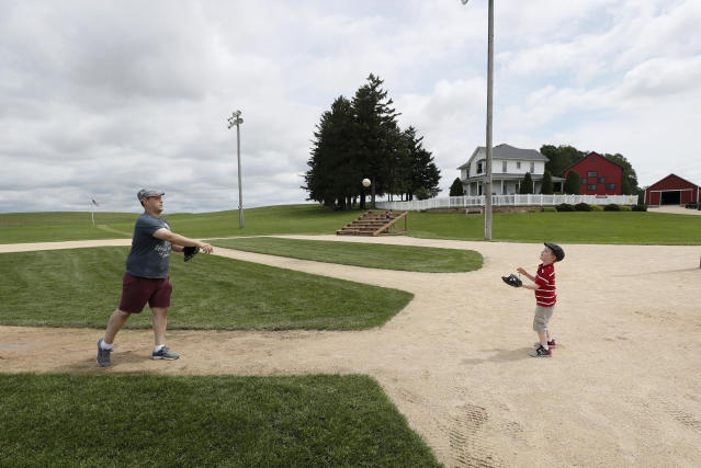 Jeremiah Bronson, of Ames, Iowa, plays catch with his sone Ben, right, on the field at the Field of Dreams movie site, Friday, June 5, 2020, in Dyersville, Iowa. Major League Baseball is building another field a few hundred yards down a corn-lined path from the famous movie site in eastern Iowa but unlike the original, it's unclear whether teams will show up for a game this time as the league and its players struggle to agree on plans for a coronavirus-shortened season. (AP Photo/Charlie Neibergall)