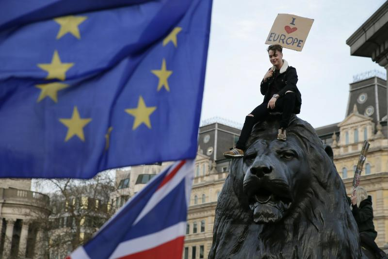 A demonstrator sits on one of the lions in Trafalgar Square during a Peoples Vote anti-Brexit march in London, Saturday, March 23, 2019. The march, organized by the People's Vote campaign is calling for a final vote on any proposed Brexit deal. This week the EU has granted Britain's Prime Minister Theresa May a delay to the Brexit process. (AP Photo/Tim Ireland)