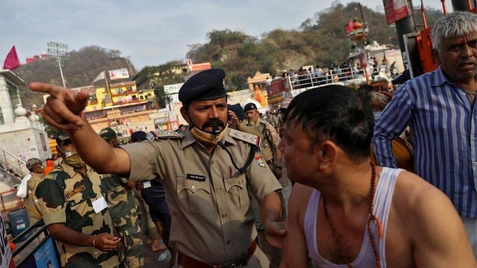 A police officer asks a devotee to leave after a dip