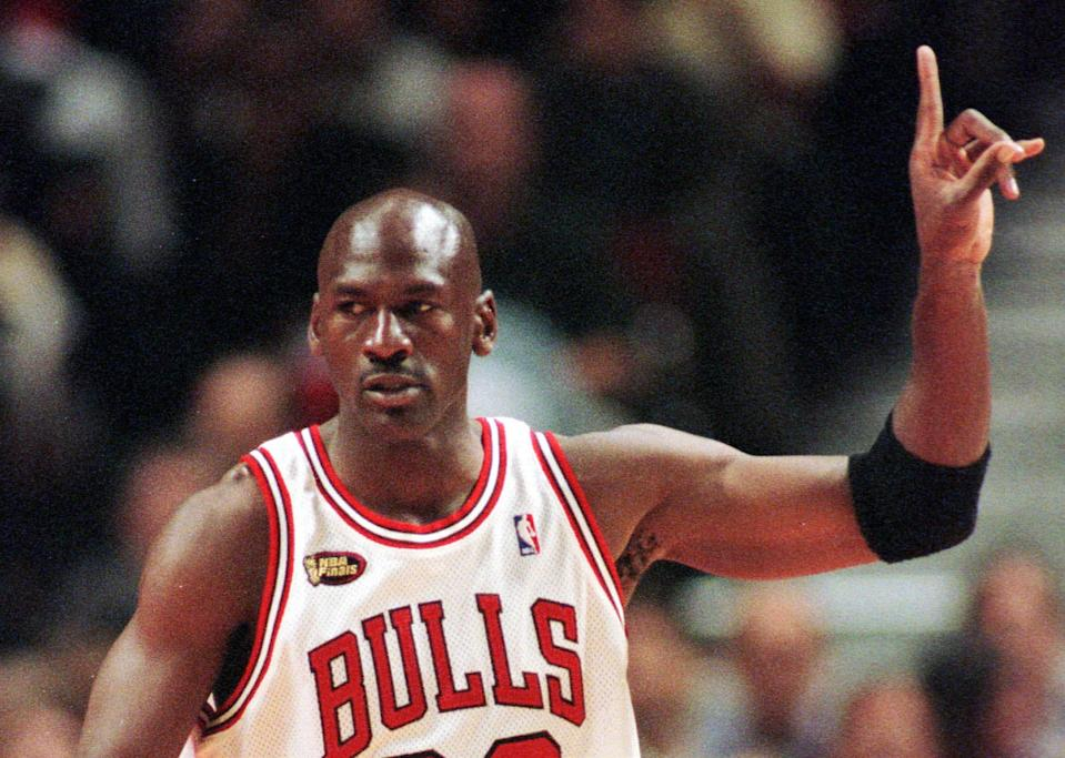 Chicago Bulls guard Michael Jordan signals to his teammates during the first quarter of Game 5 of the NBA finals in Chicago, Friday, June 12, 1998. (AP Photo/Beth A. Keiser)