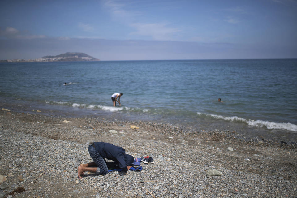 A boy prays before taking a swim in the Moroccan northern town of Fnideq, near the border of Morocco and Spain, at the Spanish enclave of Ceuta, on Tuesday, May 18, 2021. (AP Photo/Mosa'ab Elshamy)
