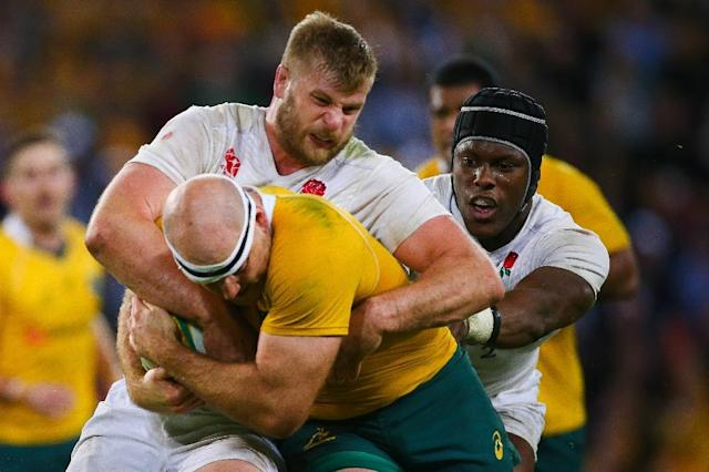 England's George Kruis (C) tackles Australia's Stephen Moore (R) during the rugby union international in Brisbane on June 11, 2016 (AFP Photo/Patrick Hamilton)