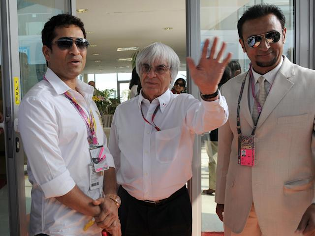 Indian cricketer Sachin Tendulkar (L), Indian Bollywood star Gulshan Grovar (R) and President and CEO of Formula One Management and Formula One Administration Bernie Ecclestone (C) pose for media in paddock prior to the Formula One's Indian Grand Prix at the Buddh International circuit in Greater Noida on October 30, 2011. AFP PHOTO/ Prakash SINGH (Photo credit should read PRAKASH SINGH/AFP/Getty Images)