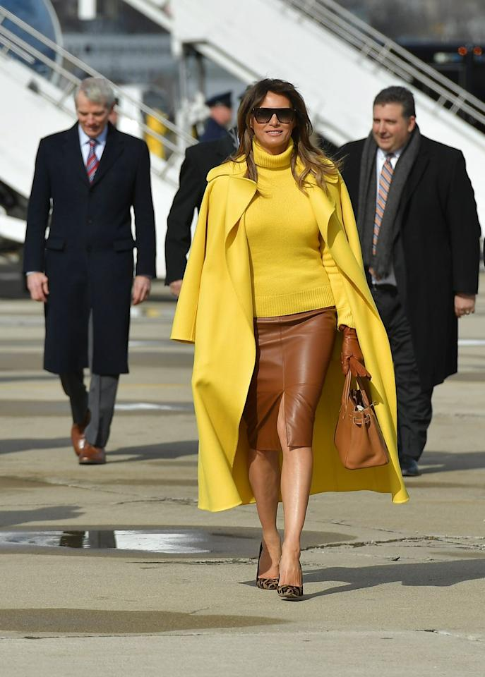 The First Lady wore a yellow turtleneck sweater with a matching coat by Ralph Lauren with a brown leather skirt by Herve Pierre for a trip to Ohio, where she visited Cincinnati Children's Hospital.
