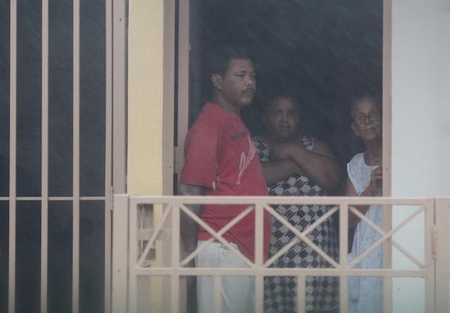 <p>People look out from a house as Hurricane Irma howls past Puerto Rico after thrashing several smaller Caribbean islands, in Fajardo, Puerto Rico, Sept. 6, 2017. (Photo: Alvin Baez/Reuters) </p>