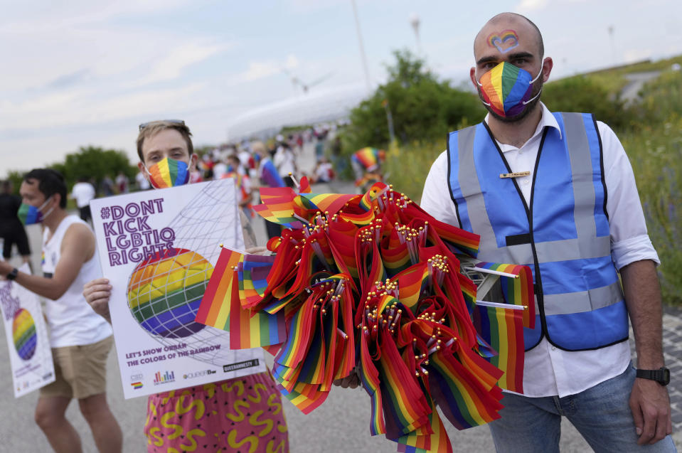 A man offers LGBT pride flags to football supporters outside the stadium before the Euro 2020 soccer championship group F match between Germany and Hungary at the Allianz Arena in Munich, Germany,Wednesday, June 23, 2021. (AP Photo/Matthias Schrader)