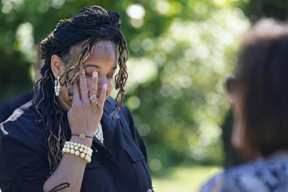 Edwina Frances Martin, Staten Island's public administrator of estates, wipes away tears as she says a few words during a burial for four people at a cemetery in the Staten Island borough of New York, Thursday, June 17, 2021. The deceased died during the coronavirus pandemic and were being stored at a temporary morgue in Brooklyn. The facility is out of sight and mind for many as the city celebrates its pandemic progress but stands as a reminder of the loss, upheaval and wrenching choices the virus inflicted in one of its deadliest U.S. hotspots. (AP Photo/Seth Wenig)