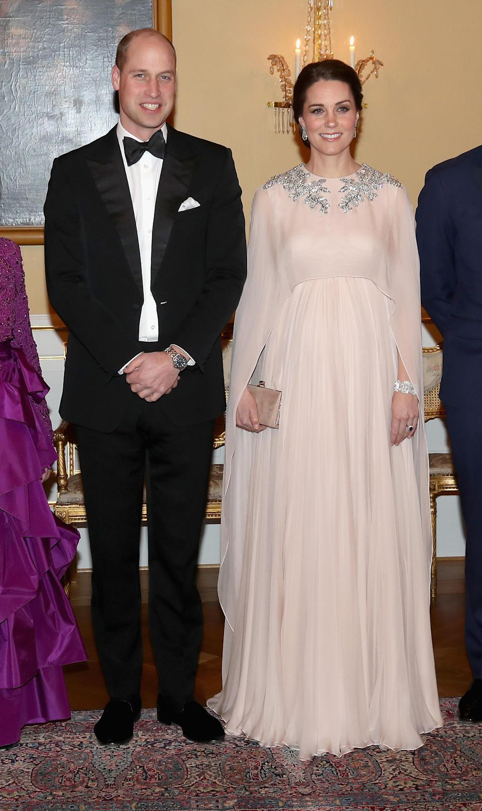 """<p>For a dinner at Stockholm's royal palace during the couple's Scandinavian tour, the Duchess of Cambridge wore a sheer Alexander McQueen cape dress. For an idea of price, a berry-hued version currently <a rel=""""nofollow noopener"""" href=""""https://www.harrods.com/en-gb/alexander-mcqueen/embellished-silk-cape-gown-p000000000006016275?ranMID=36666&ranEAID=TnL5HPStwNw&ranSiteID=TnL5HPStwNw-SJkaa2WAUdbrhHUqL7cxJg&cid=ls_uk&utm_source=Affiliate&utm_medium=RakutenAffiliate&utm_campaign=TnL5HPStwNw&utm_content=10&siteID=TnL5HPStwNw-SJkaa2WAUdbrhHUqL7cxJg"""" target=""""_blank"""" data-ylk=""""slk:retails"""" class=""""link rapid-noclick-resp"""">retails</a> at £7,499. She finished the evening look with a £1,142.85 Jimmy Choo clutch. <em>[Photo: Getty]</em> </p>"""