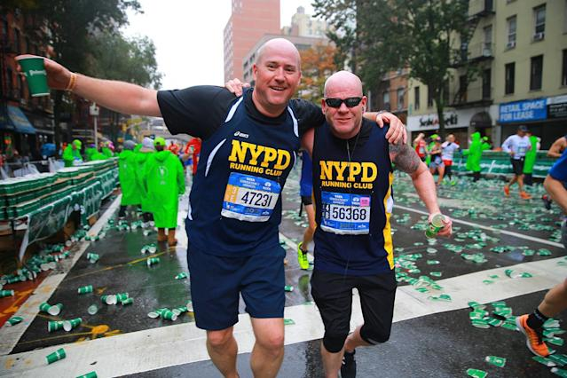 <p>Two members of the NYPD running club break for water and a photo during the 2017 New York City Marathon, Nov. 5, 2017. (Photo: Gordon Donovan/Yahoo News) </p>