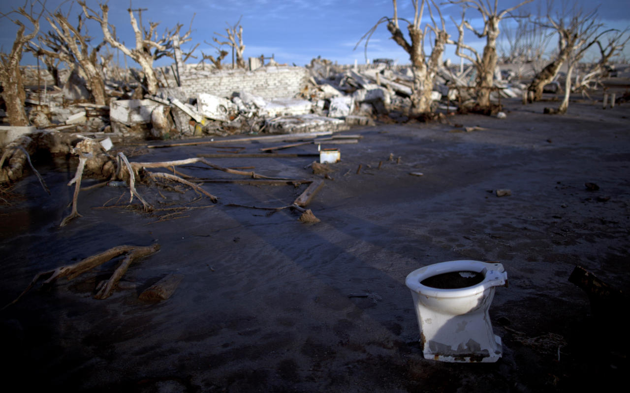 In this May 7, 2013 photo, a toilet lays among the ruins of the village of Epecuen, which once was submerged in water in Argentina. Epecuen was once a bustling little lakeside resort, where 1,500 people served 20,000 tourists a season. During Argentina's golden age, the same trains that carried grain to the outside world brought visitors from the capital to relax in Epecuen's saltwater baths and spas. (AP Photo/Natacha Pisarenko)
