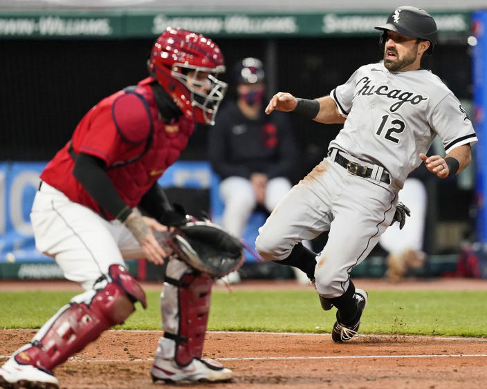 Chicago White Sox's Adam Eaton, right, scores as Cleveland Indians' Roberto Perez, left, waits for the ball in the sixth inning in a baseball game, Tuesday, April 20, 2021, in Cleveland. (AP Photo/Tony Dejak)