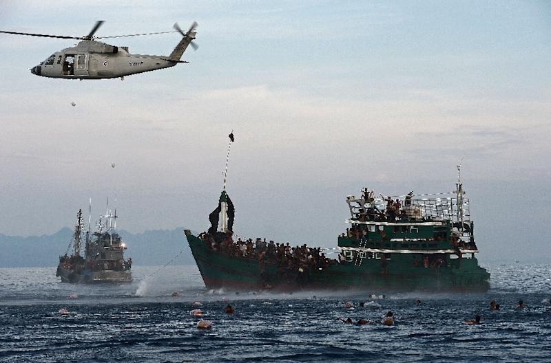 Rohingya migrants swimming to collect food supplies dropped by a Thai army helicopter after they jumped from a boat (R) drifting in Thai waters off the southern island of Koh Lipe in the Andaman sea (AFP Photo/Christophe Archambault)
