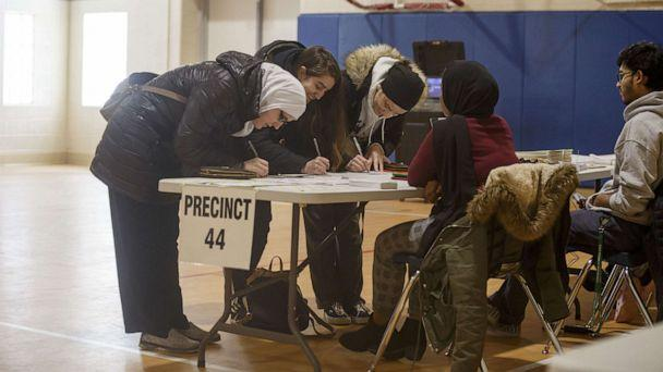PHOTO: Azemina Hodzic prepares to vote with her two daughters, Amra Hodzic and Lejla Hodzic at a polling place at Cromie Elementary School on March 10, 2020, in Warren, Mic. (Elaine Cromie/Getty Images)