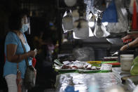A woman wears a mask and face shield as a measure to help curb the spread of COVID19 as she buys fish at a public market on Sunday, Aug. 2, 2020, in Quezon city, Philippines. Coronavirus infections in the Philippines continues to surge Sunday as medical groups declared the country was waging a losing battle against the contagion and asked the president to reimpose a lockdown in the capital. (AP Photo/Aaron Favila)