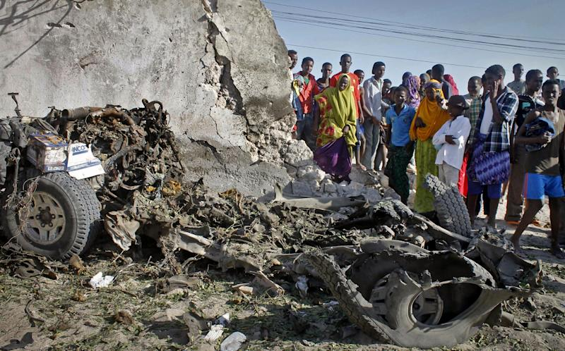 Somalis stand over the wreckage of a car following a blast at a restaurant near the beach in Mogadishu, Somalia Friday, March 1, 2013. A suicide bomber detonated explosives inside the seaside restaurant in Somalia's capital on Friday, killing himself and one diner and wounding six others, a police official said, nearby to where another restaurant was attacked in mid-February. (AP Photo/Farah Abdi Warsameh)