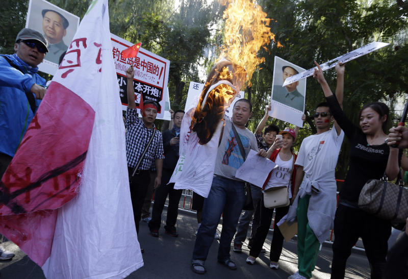 Chinese protesters burn a Japanese flag near posters claiming Diaoyu islands, as known in China and Senkaku in Japan,   belong to China and to fire upon Japan during a protest near the Japanese Embassy in Beijing, China, Tuesday, Sept. 18, 2012. The 81st anniversary of a Japanese invasion brought a fresh wave of anti-Japan demonstrations in China on Tuesday, with thousands of protesters venting anger over the colonial past and a current dispute involving contested islands in the East China Sea. (AP Photo/Ng Han Guan)