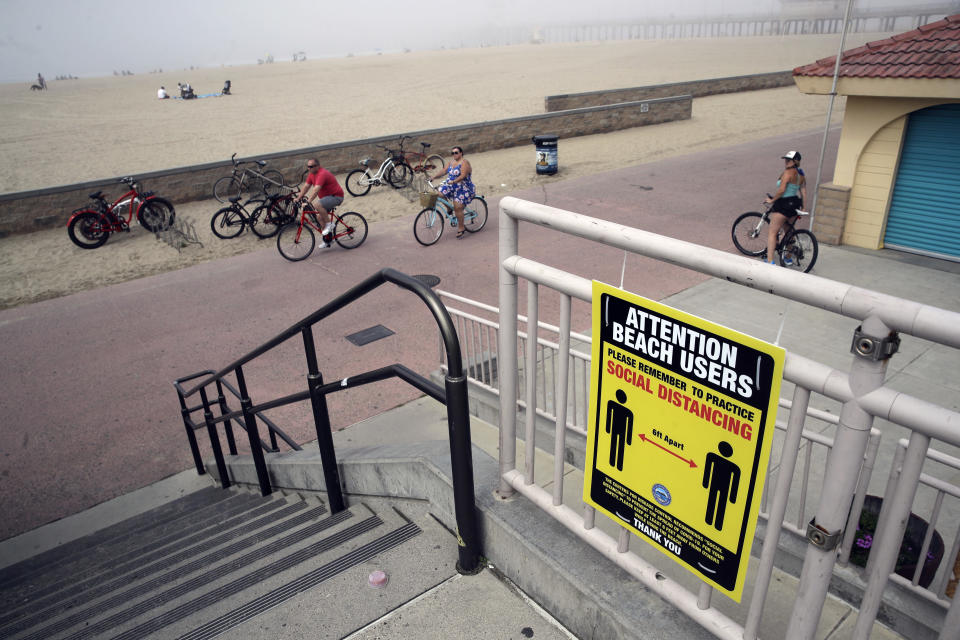 FILE - In this April 26, 2020, file photo, a sign encourages people to practice social distance in Huntington Beach, Calif. As the weather warms, some already have begun venturing outside in larger numbers, despite guidance to stay home. Government officials say they aim to manage public health risks in a way that allows for a gradual return to normal, but with the course of the outbreak still unknown, nobody is sure what summer will bring. (AP Photo/Marcio Jose Sanchez, File)