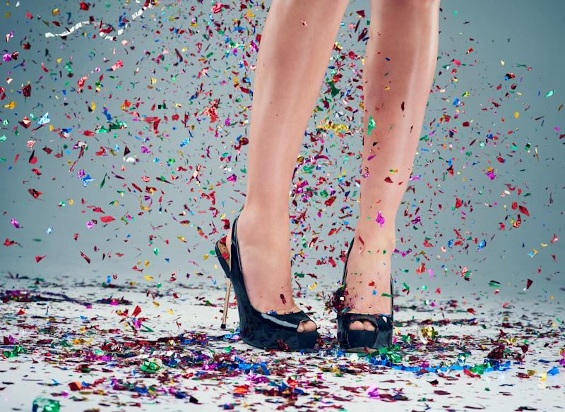 Studio shot of a young woman's legs in a pair of heels with confetti falling around against a grey background