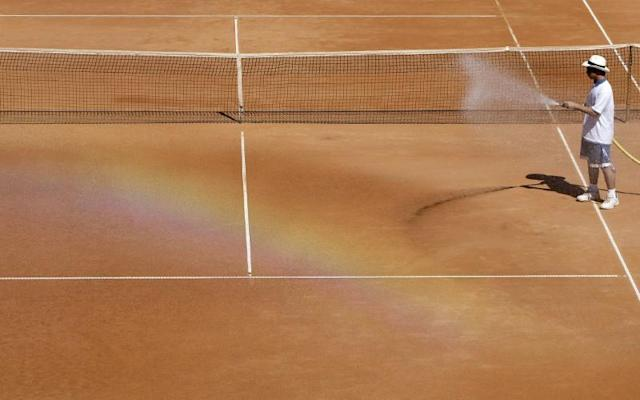 A rainbow is visible as groundsman sprays water over the court before the second round match at the Swiss Open ATP tennis tournament in Gstaad