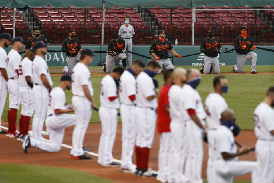 The Boston Red Sox and the Baltimore Orioles line up on the base lines during a tribute to the Black Lives Matter movement before an opening day baseball game at Fenway Park, Friday, July 24, 2020, in Boston. (AP Photo/Michael Dwyer)