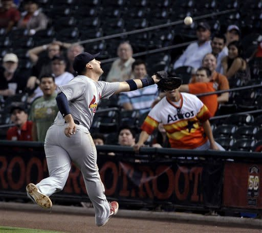St. Louis Cardinals first baseman Allen Craig reaches for a foul ball from Houston Astros' Matt Downs in the ninth inning of a baseball game Tuesday, Sept. 25, 2012, in Houston. Craig could not catch the ball, and Downs eventually struck out. The Cardinals won 4-0. (AP Photo/Pat Sullivan)