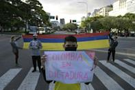 """Colombians stand in front of their country's consulate in Buenos Aires, Argentina and hold up a sign reading, """"Colombia is under dictatorship"""" during a demonstration against the Colombian government"""