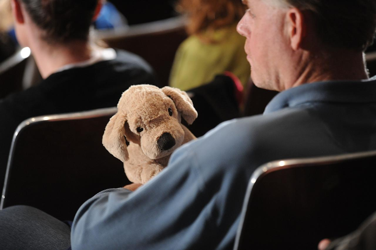NEWTOWN, CT - DECEMBER 16:  A man holds a stuffed dog before U.S. President Barack Obama speaks at an interfaith vigil for the shooting victims from Sandy Hook Elementary School on December 16, 2012 at Newtown High School in Newtown, Connecticut. Twenty-six people were shot dead, including twenty children, after a gunman identified as Adam Lanza opened fire at Sandy Hook Elementary School. Lanza also reportedly had committed suicide at the scene. A 28th person, believed to be Nancy Lanza, found dead in a house in town, was also believed to have been shot by Adam Lanza. (Photo by Olivier Douliery-Pool/Getty Images)