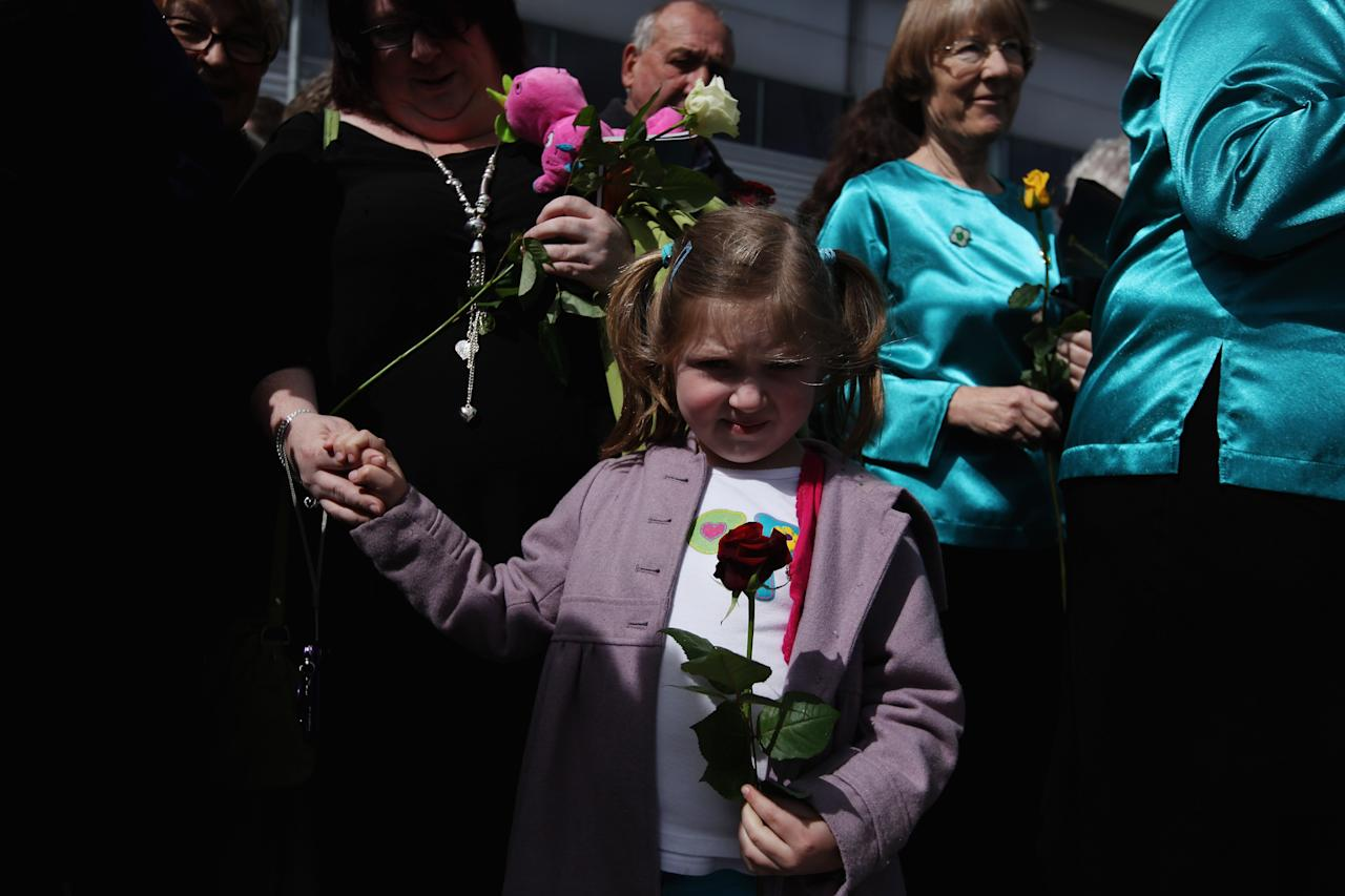 Friends and family of some of the descendants of those who perished when RMS Titanic sank, wait to throw flowers into births 43 and 44 at Southampton Dock during a Centenary Memorial on April 10, 2012 in Southampton, England. The births mark the departure point of RMS Titanic when it set sail one hundred years ago today. The maiden voyage of the ill-fated passenger liner Titanic ended when she sank after hitting an iceberg in the Atlantic on the night of April 14, 1911 with the loss of 1517 lives.  (Photo by Dan Kitwood/Getty Images)