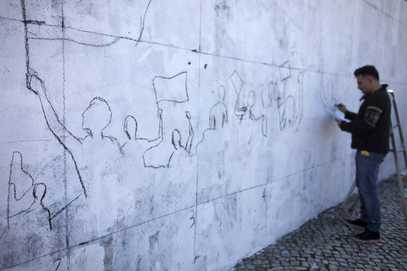 """In a Feb. 24, 2013 photo filmmaker Alexandre Azinheira draws the outline of a mural calling for participation in anti-austerity protests in Lisbon. Portuguese unhappy about the center-right government's relentless austerity drive aren't just getting mad, they're getting even - in imaginative ways. With his retired parents unable to meet mortgage payments on their home, Azinheira said he was spurred to act because the government had """"betrayed"""" the Portuguese. (AP Photo/Armando Franca)"""