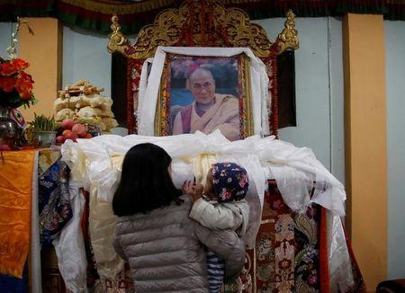 A Tibetan woman carrying a child offers prayer on the portrait of exiled Tibetan spiritual leader, the Dalai Lama, during a function to mark the Tibetan Uprising Day at the Tibetan Refugee camp in Lalitpur