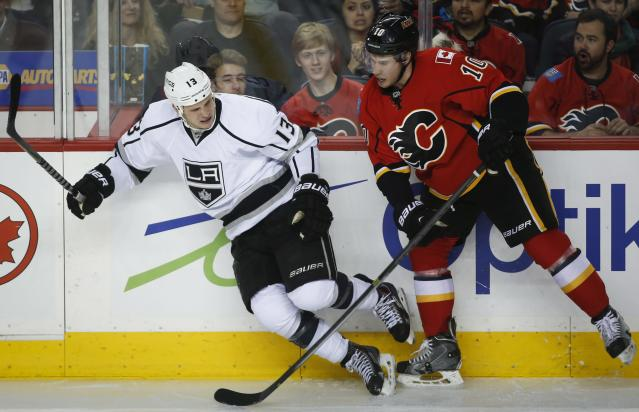 Los Angeles Kings' Kyle Clifford, left, runs into Calgary Flames' Corban Knight during second period NHL hockey action in Calgary, Alberta, Monday, March 10, 2014. (AP Photo/The Canadian Press, Jeff McIntosh)