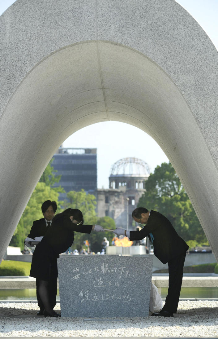 Hiroshima Mayor Kazumi Matsui, right, dedicates the list of the victims of atomic bombing to the cenotaph during a ceremony to mark the 73rd anniversary of the bombing at Hiroshima Peace Memorial Park in Hiroshima, western Japan, Monday, Aug. 6, 2018. Matsui raised concerns in his peace address about the rise of egocentric policies in the world and warned against the idea of nuclear deterrence as a threat to global security. The Atomic Bomb Dome is seen in the background. (Yohei Nishimura/Kyodo News via AP)